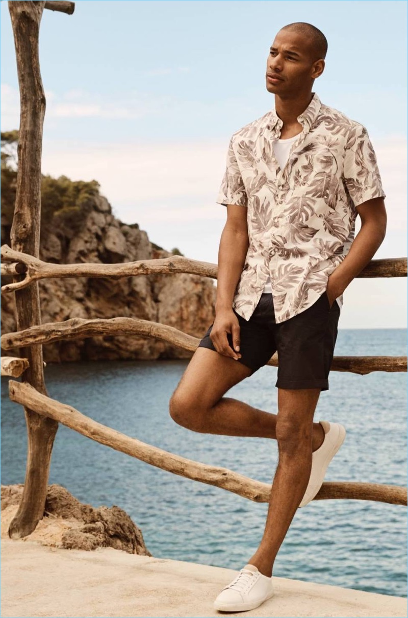 Connecting with H&M, Sacha M'Baye wears a patterned short-sleeve shirt with chino shorts.