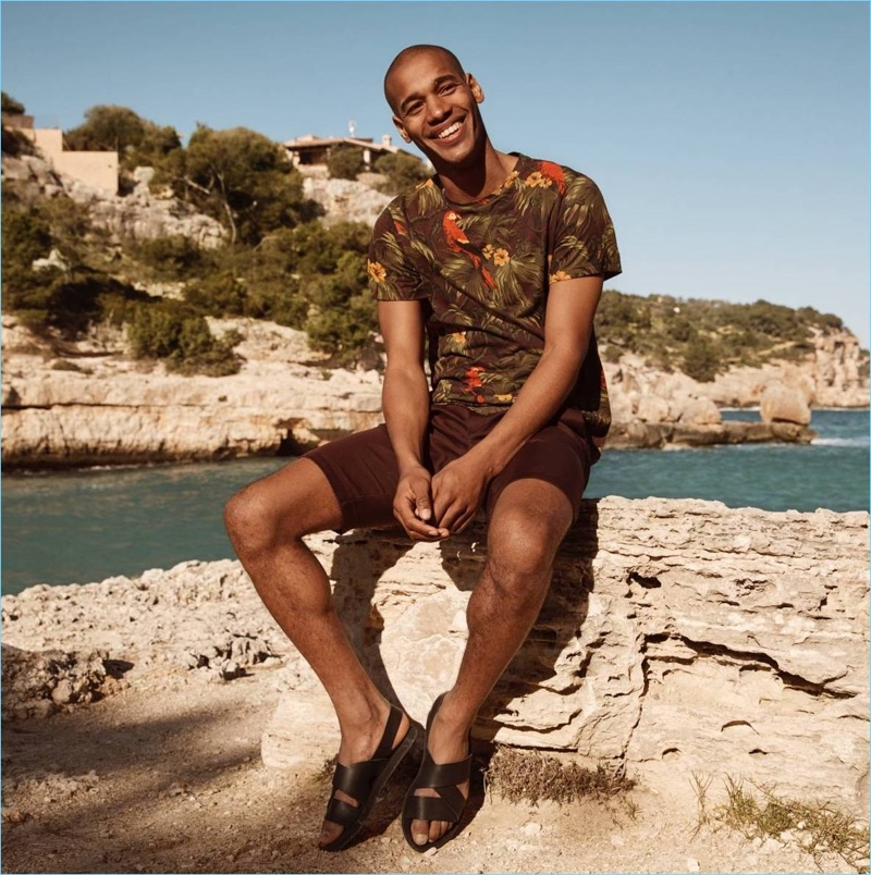 All smiles, Sacha M'Baye sports a tropical print t-shirt, burgundy chino shorts, and sandals by H&M.