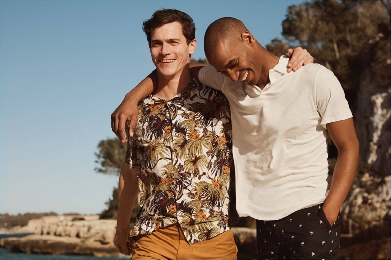 Left to Right: Vincent LaCrocq wears a tropical print shirt with chino shorts by H&M. Sacha M'Baye sports a white H&M polo shirt with palm tree print chino shorts.