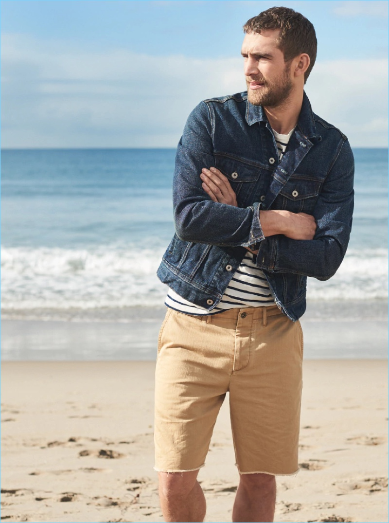 "Taking to the beach, Will Chalker wears J.Crew's 9"" distressed officer's shorts in golden khaki."