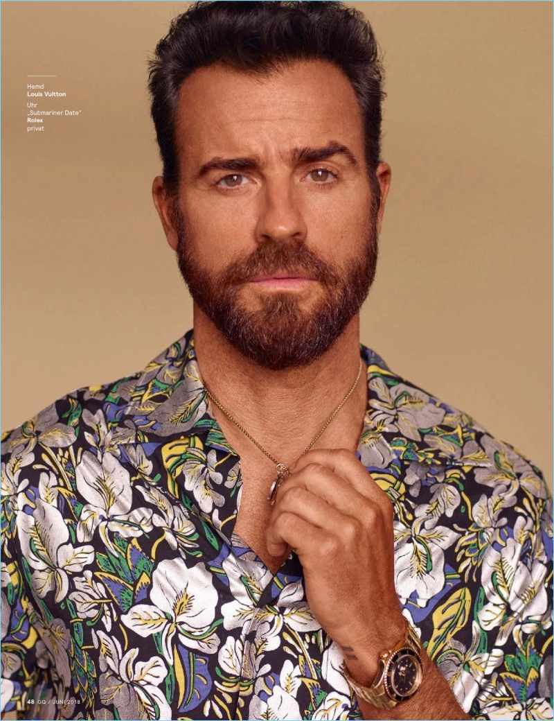Front and center, Justin Theroux wears a Louis Vuitton shirt and Rolex watch.