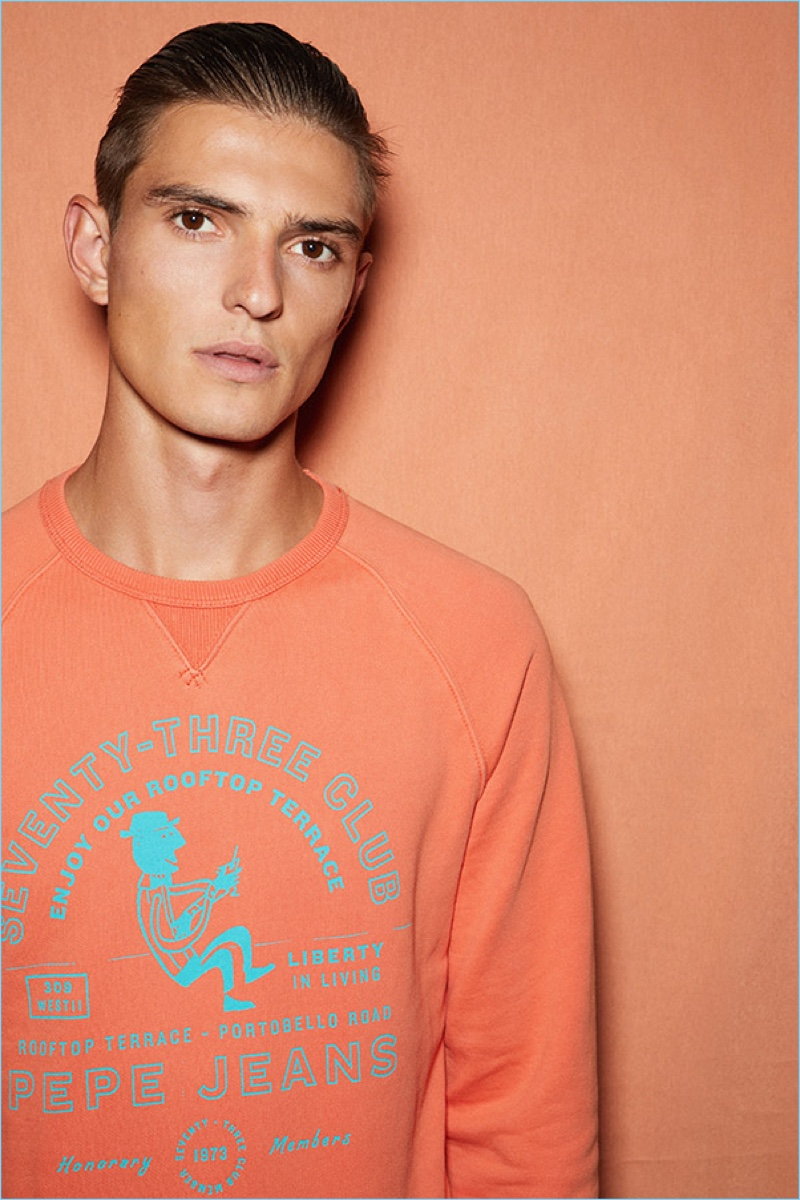 Model Guerrino Santulliana wears an orange pullover from Pepe Jeans' pre-fall 2018 lineup.