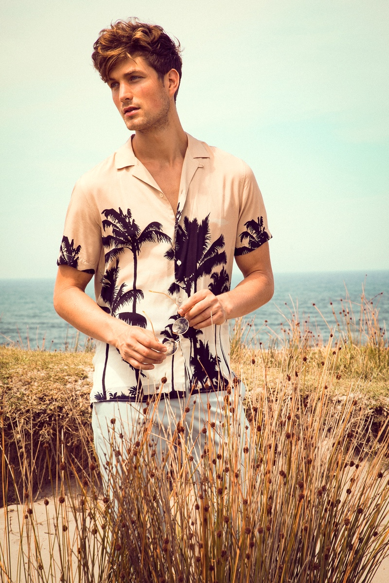 Embracing a summer mood, Saxon wears a Zara camp-collar palm tree print shirt with pants.