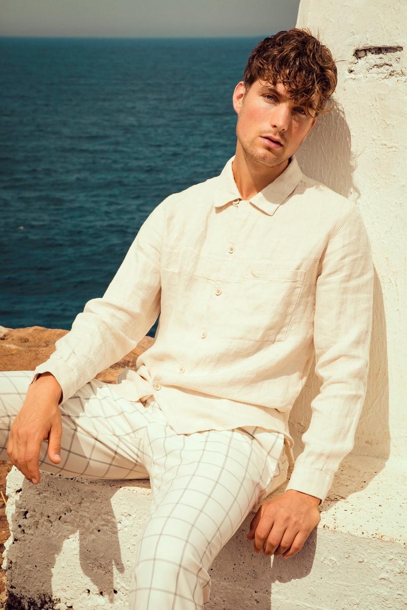 Donning summer neutrals, Saxon wears a linen shirt and windowpane print pants from Zara.
