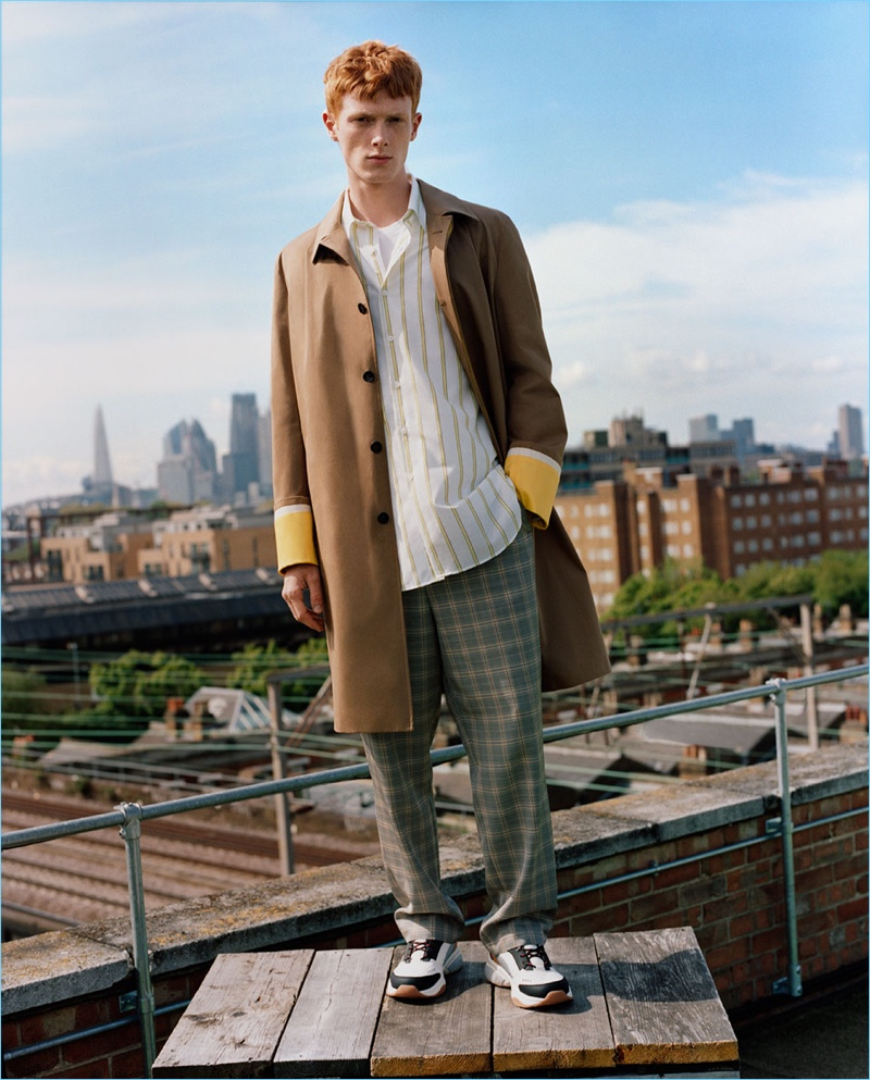 Linus Wordemann dons a car coat with a striped shirt, check pants, and sneakers from Zara Man.