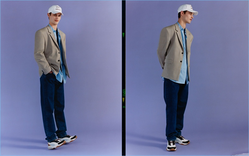 Kit Butler dons relaxed jeans with a shirt, blazer, sneakers, and a cap from Zara Man.
