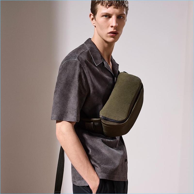 Model Tim Schuhmacher sports Dunhill's trendy belt bag with a suede shirt.