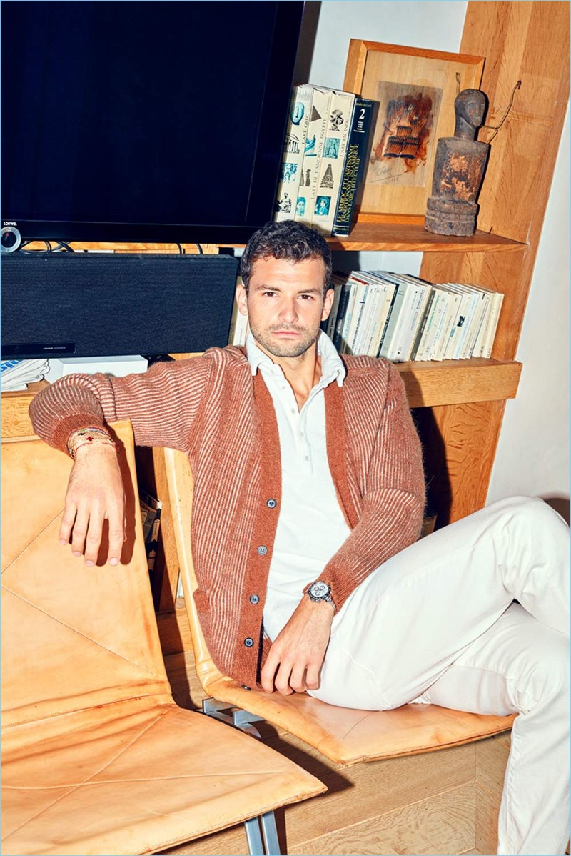 Relaxing, Grigor Dimitrov sports a Lanvin cardigan, Massimo Alba polo, and white Burberry jeans.