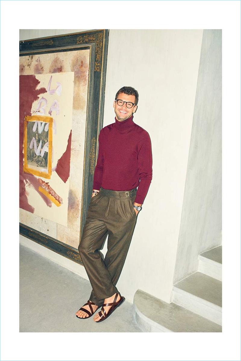 A chic vision, Grigor Dimitrov dons a Boglioli turtleneck sweater, Rubinacci trousers, and Ray-Ban glasses.
