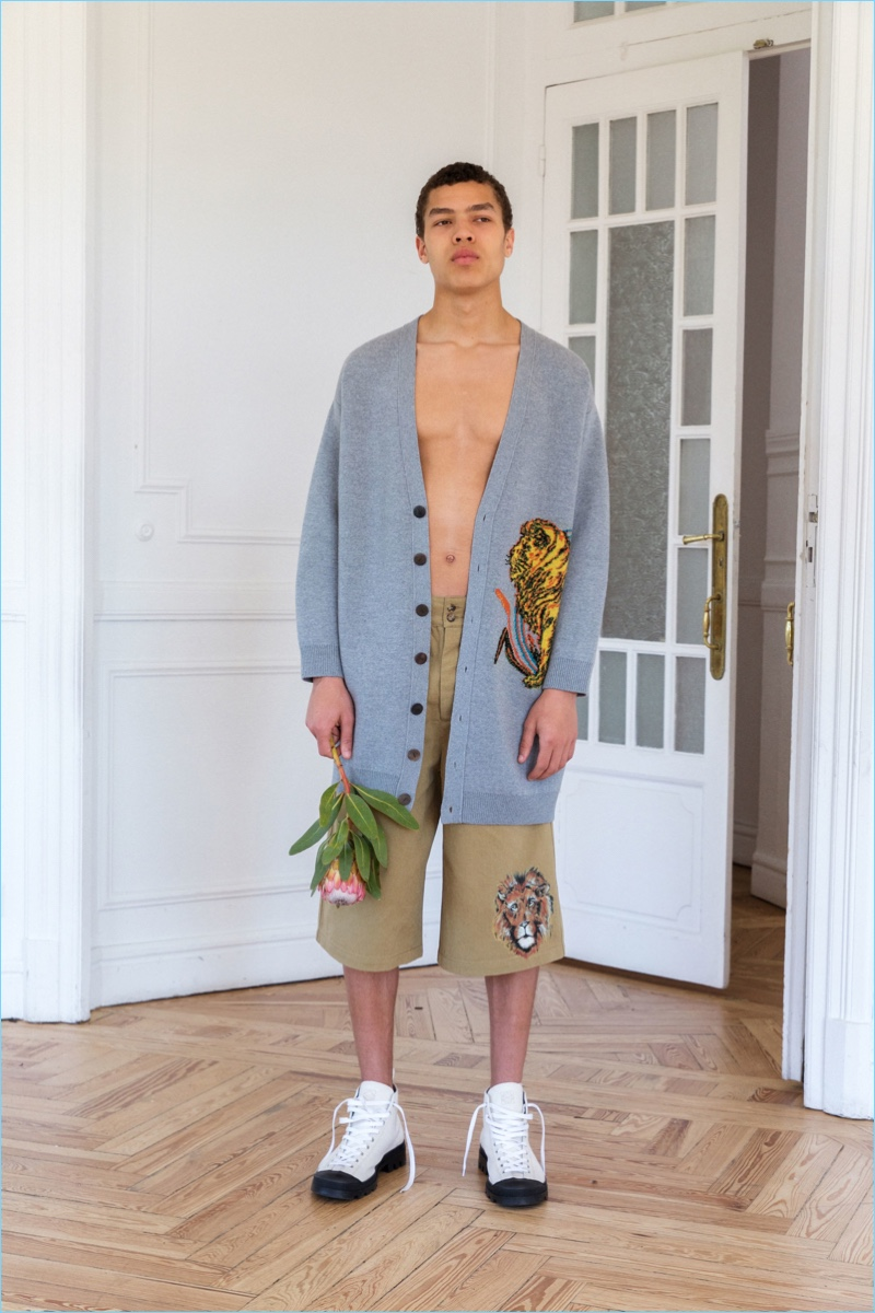 Louis Griffiths dons an oversized Loewe cardigan and shorts adorned with a lion.