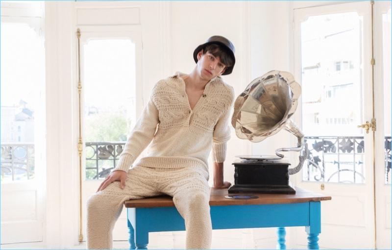 Sporting a bucket hat, Oscar Ruebman wears light colored knitwear by Loewe.