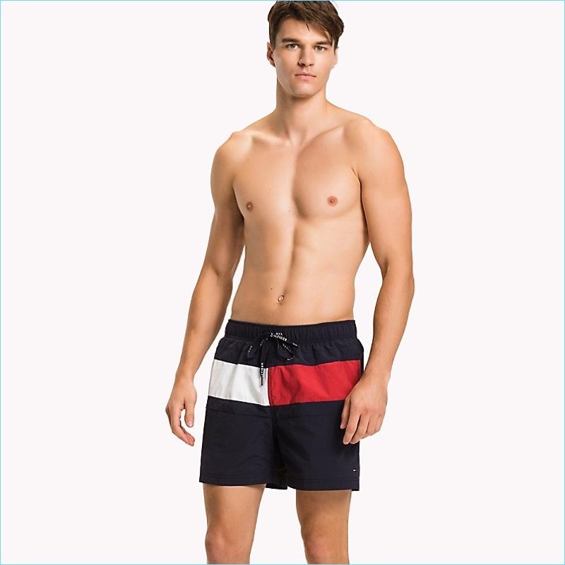 Arran Sly wears Tommy Hilfiger's Flag mid-length swim trunks.