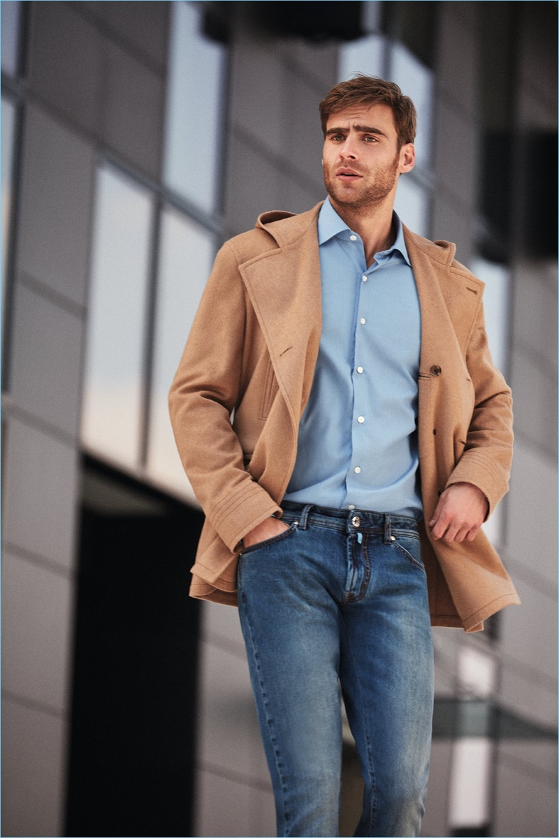 Embracing smart but contemporary style, George Alsford wears denim jeans with a dress shirt.
