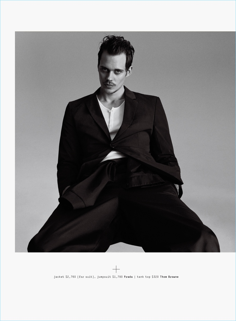 A chic vision, Bill Skarsgård dons a Prada suit jacket and jumpsuit with a Thom Browne tank.
