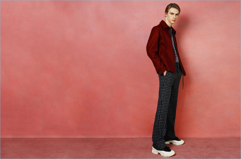 Dominik Sadoch wears a striped Lanvin t-shirt and wool jacket. He also sports Givenchy trousers and sneakers by Raf Simons x Adidas Originals.