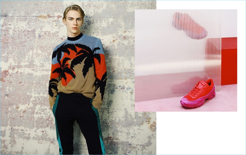 A chic vision, Dominik Sadoch dons a Hawaiian print sweater from Valentino. The blond model also sports a Givenchy t-shirt and Lanvin track pants. Pictured right: Raf Simons x Adidas sneakers.