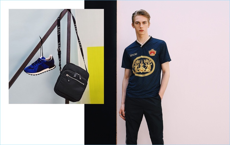 Embracing simple style, Dominik Sadoch wears a football t-shirt and track pants by Versace. Pictured left: Maison Margiela sneakers and a Valentino cross-body bag.