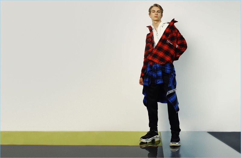 Making a checked statement, Dominik Sadoch wears shirts and a sweatshirt by Off-White. AMI track pants and Balenciaga sneakers complete his look.