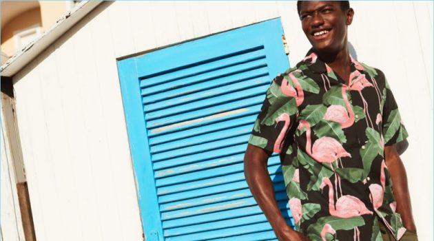 Hamid Onifade reunites with H&M. He wears a relaxed fit flamingo print shirt with cargo shorts.