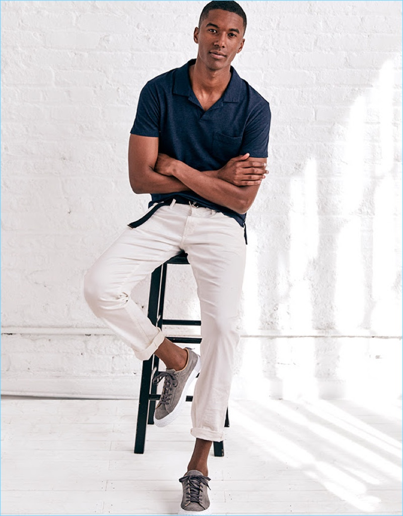 Model Claudio Monteiro wears a Todd Snyder polo shirt, selvedge white jeans, and a double ring leather belt. Todd Snyder x PF Flyers sneakers complete Claudio's look.