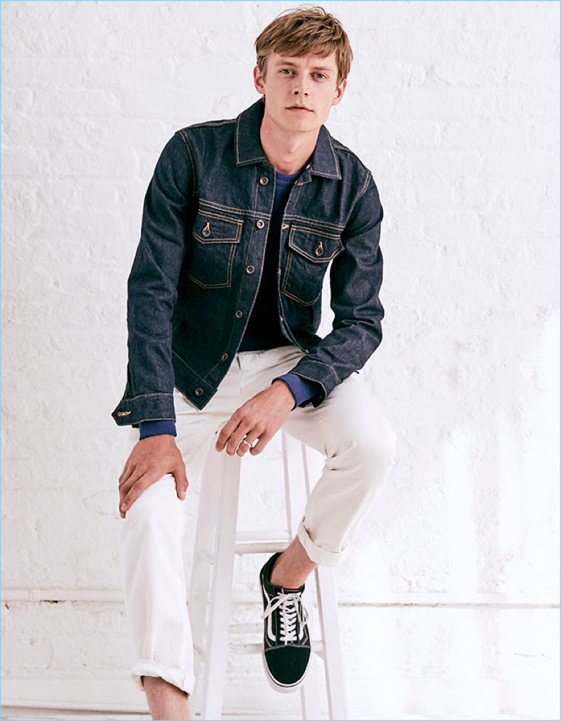 Janis Ancens sports Todd Snyder Japanese selvedge chino officer pants in white. He also wears a Todd Snyder Made in Los Angeles denim jacket with a sweatshirt from the designer's Champion collaboration. Vans Old Skool sneakers complete Janis' look.