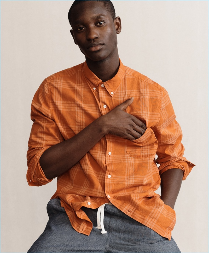 Charles Oduro wears a J.Crew overdyed plaid shirt and stretch dock shorts in chambray.