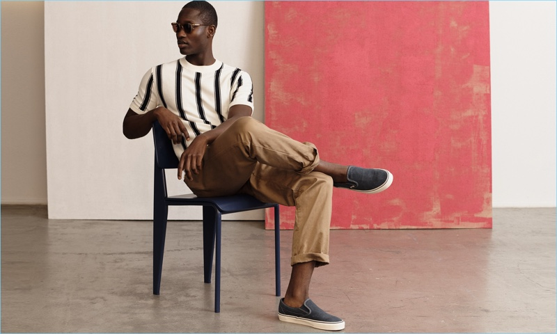 Embracing summer style, Charles Oduro wears a striped J.Crew top, stretch chinos, and sunglasses with Vans slip-on sneakers.