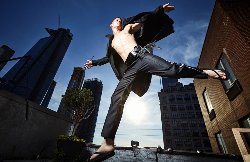 Jordan wears belt Bond Hardware, sandals Dan Ward Wear, trench Versace, and pants Dsquared2.