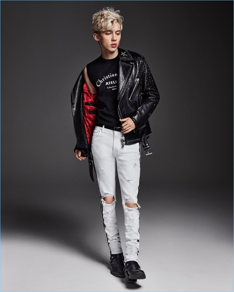 A cool vision, Troye Sivan wears a sleeveless Dior Homme sweater with a Valentino leather biker jacket. He also rocks Amiri jeans and Saint Laurent boots.