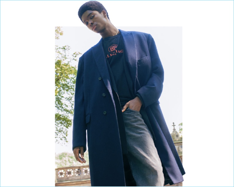 Making an oversized statement, Alton Mason sports a coat, jacket, t-shirt, and jeans, all by Balenciaga.
