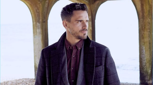 A sleek vision, Arthur Kulkov dons a Brunello Cucinelli suit, overcoat, and shirt.