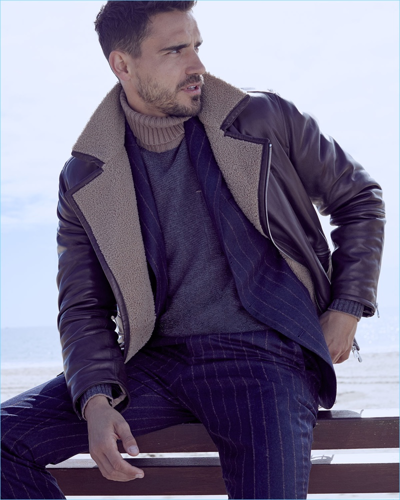 Suave, Arthur Kulkov layers in a Brunello Cucinelli pinstripe suit, shearling-lined moto jacket, and turtleneck sweater.
