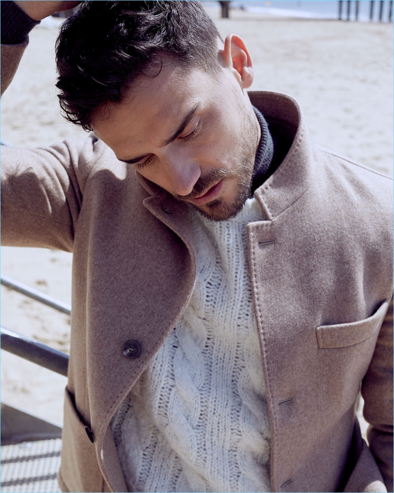Model Arthur Kulkov sports a Brunello Cucinelli patch-pocket jacket, cable-knit sweater, and wool-cashmere turtleneck.