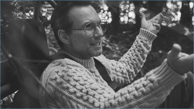 A smart vision, Christian Slater dons a Brioni cable-knit sweater and Gucci glasses.