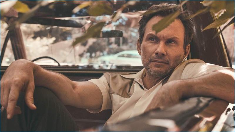 Relaxing, Christian Slater wears a Maison Margiela shirt and Maison Kitsuné trousers.