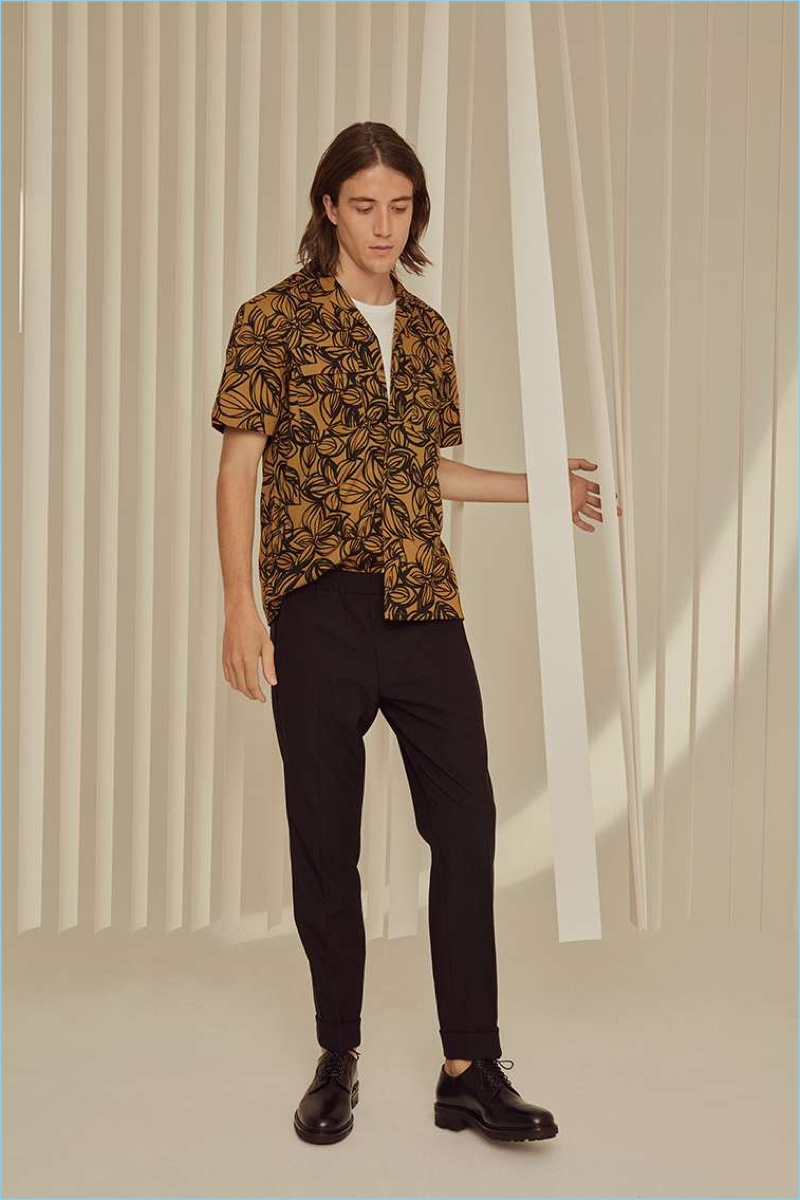 Lucian Clifforth sports a Club Monaco flower print shirt, pocket tee, trousers, and W&H officer shoes.