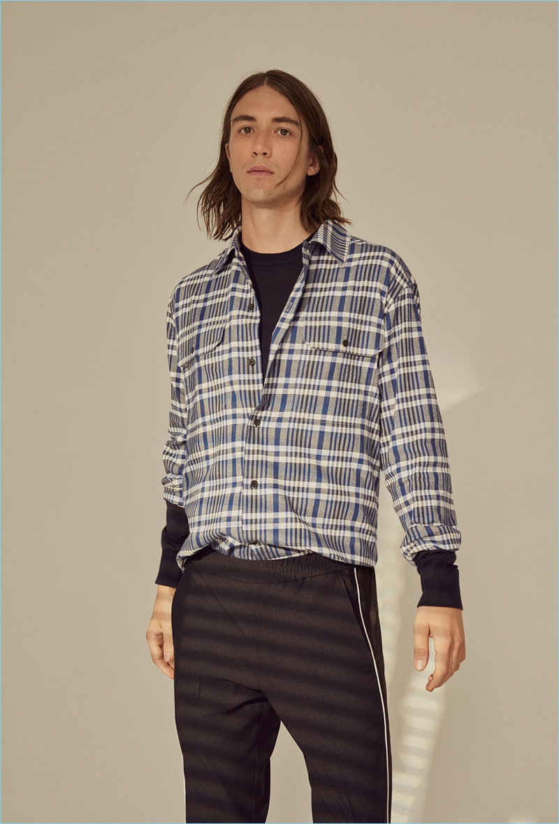 Model Lucian Clifforth wears a Club Monaco pullover, plaid shirt, and pants.