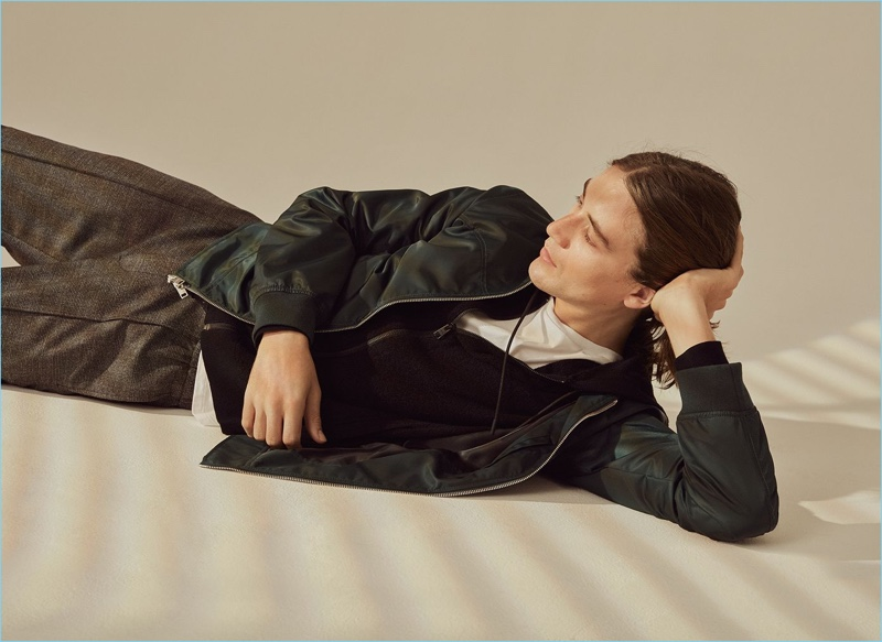 Layering for fall, Lucian Clifforth wears a bouclé hoodie, bomber jacket, and plaid trousers from Club Monaco.