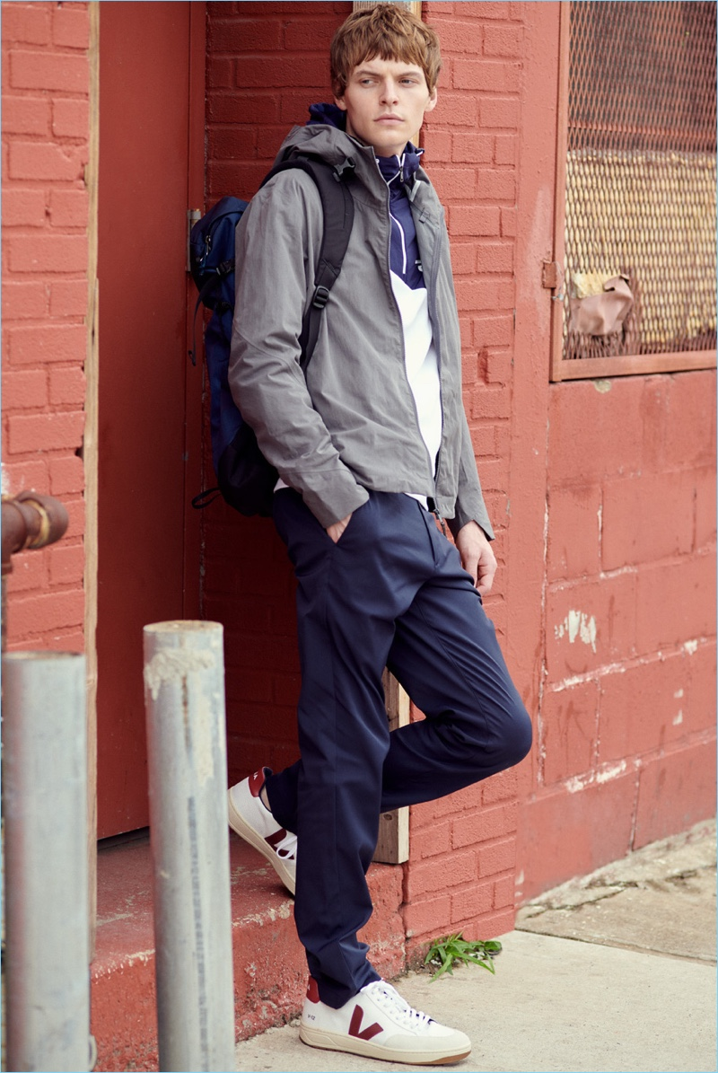 Embracing sporty style, John Hein wears a Vince pima cotton tee, POLO Ralph Lauren anorak, and Arc'Teryx Veilance Isogon jacket. The model also rocks Theory trousers, Veja sneakers, and an Arc-Teryx Brize 25 backpack.