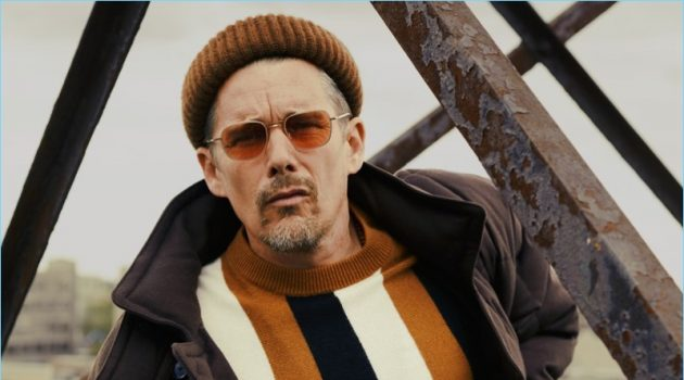 A cool vision, Ethan Hawke wears a BOSS coat, pants, and beanie. Hawke also rocks a Sandro sweater and Garrett Leight sunglasses.