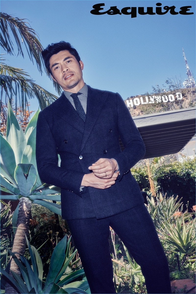 Henry Golding wears a sharp suit, shirt, and tie by Ralph Lauren.