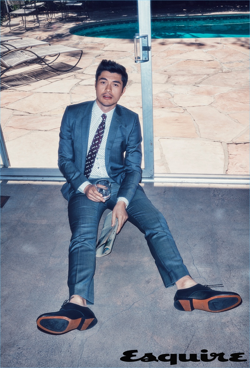 Connecting with Esquire, Henry Golding wears a shirt, suit, and shoes by Dolce & Gabbana with an Issey Miyake Men tie.