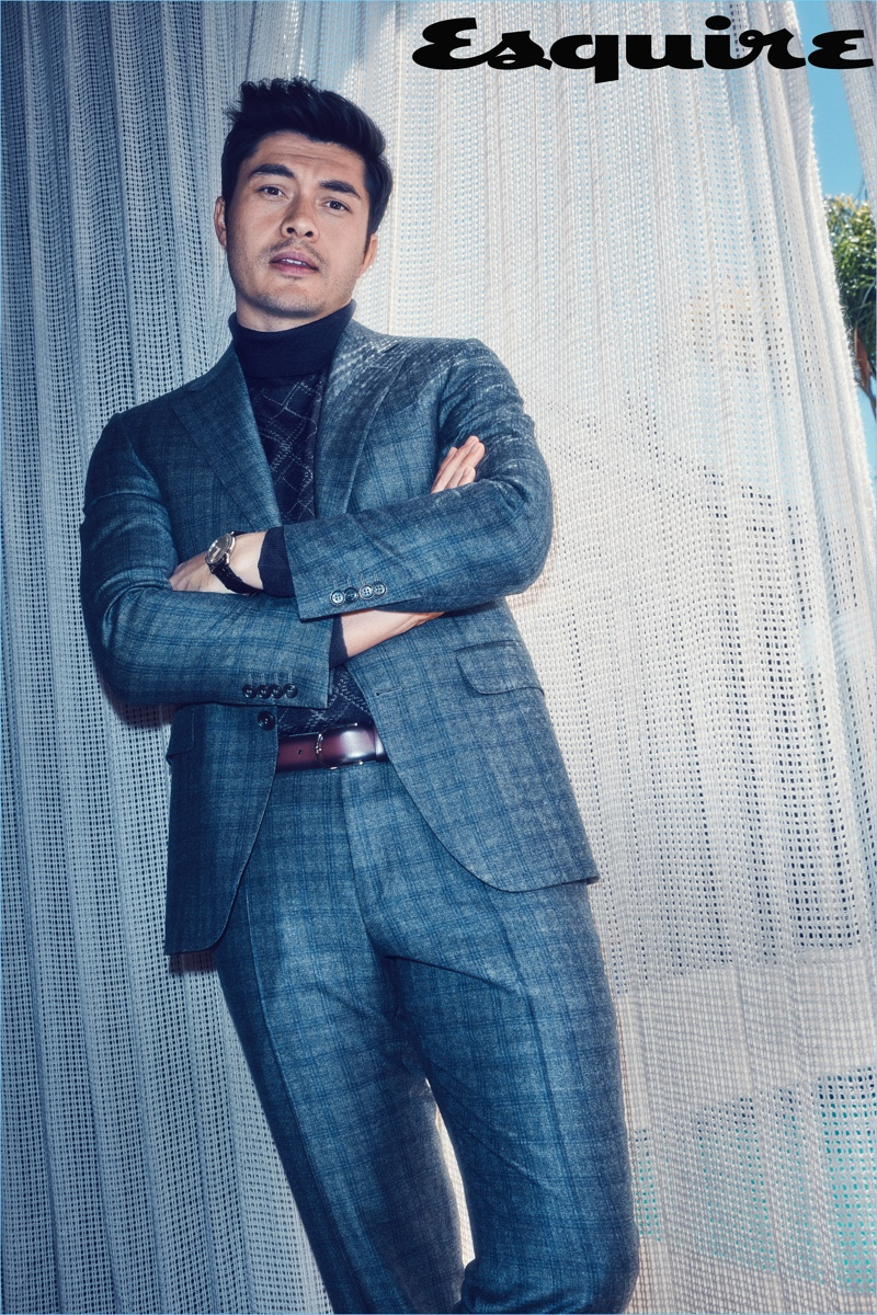 Crazy Rich Asians star Henry Golding dons a turtleneck sweater, suit, and belt by Canali. He also wears a Glashütte watch.