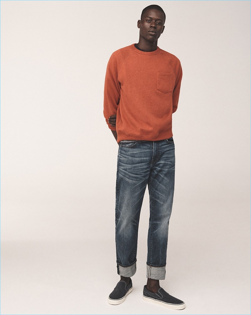 Alpha Dia wears a J.Crew sweatshirt, striped t-shirt, and 1040 athletic fit jeans with Vans sneakers.
