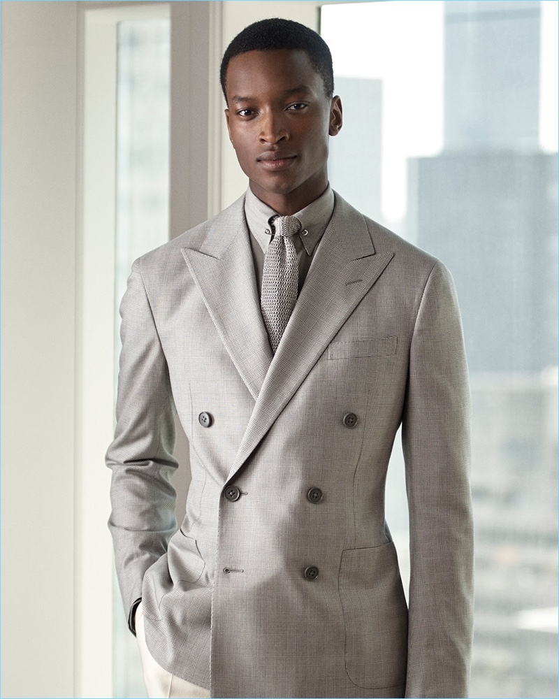 A sleek vision, Oliver Kumbi wears a houndstooth double-breasted sport coat, shirt, and knit tie from Ralph Lauren Purple Label.