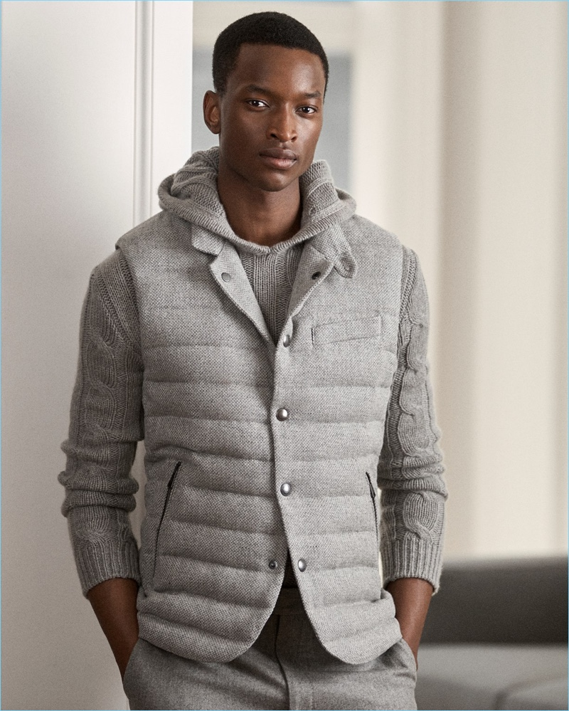 Model Oliver Kumbi layers in a grey quilted vest, hooded sweater, and wool trousers by Ralph Lauren Purple Label.