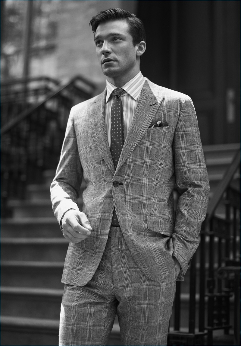 Strictly Business: Alexis Petit dons a grey suit, striped shirt, silk tie, and pocket square by Reiss.