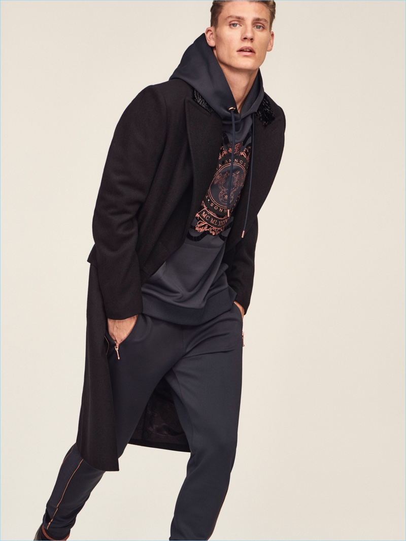 Mikkel Jensen dons a coat with a hoodie and joggers from River Island's RI30 collection.