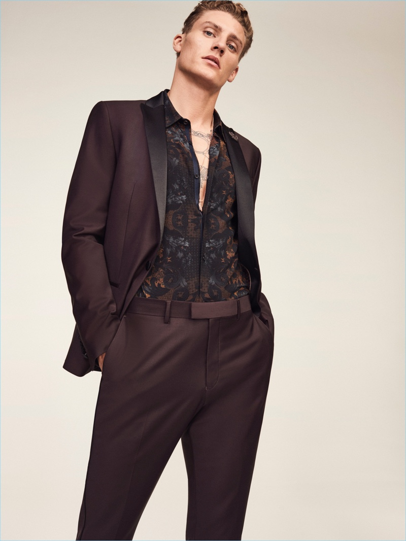 Celebrating River Island's 30th anniversary, Mikkel Jensen dons a sharp suit in burgundy with a baroque print shirt.