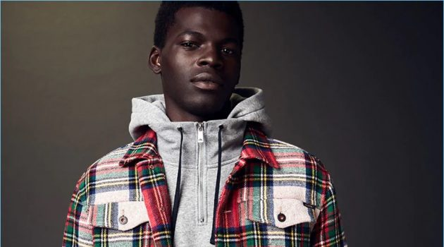 Model Evandro Laurens sports a hoodie with a tartan trucker jacket and trousers by Scotch & Soda.